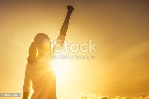 Woman with fist in the air at sunset.
