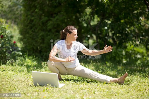 Woman practice Tai Chi Chuan  and watching online workout tutorials on the laptop  in a park.  Chinese management skill Qi's energy. solo outdoor activities. Social Distancing