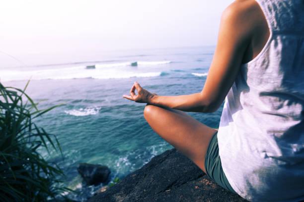 Frau praktiziert Yoga am Meer auf dem Felsen – Foto