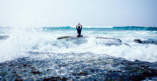 Frau üben Yoga am Meer Korallen Klippenrand gesichten die Wellen – Foto
