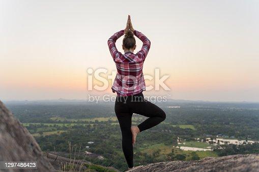 istock A woman practice yoga on the top of the Sri Lanka rock 1297486423