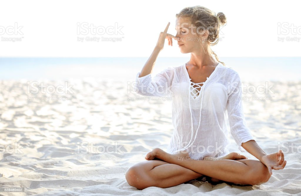 Woman practices pranayama in lotus pose on the beach stock photo