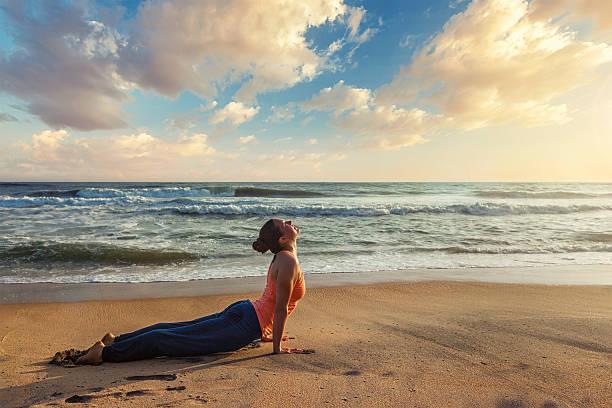 Woman practices yoga asana Urdhva Mukha Svanasana at the beach Yoga outdoors on beach - woman practices Ashtanga Vinyasa yoga Surya Namaskar Sun Salutation asana Urdhva Mukha Svanasana - upward facing dog pose on sunset. Kerala, India sun salutation stock pictures, royalty-free photos & images