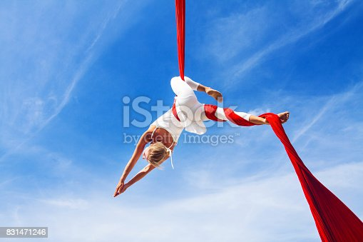 istock Woman practicing aerial silk yoga outdoors 831471246