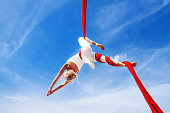 Woman practicing aerial silk yoga outdoors
