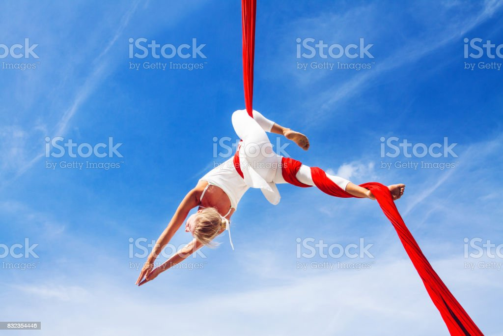 Woman practicing aerial silk yoga outdoors stock photo