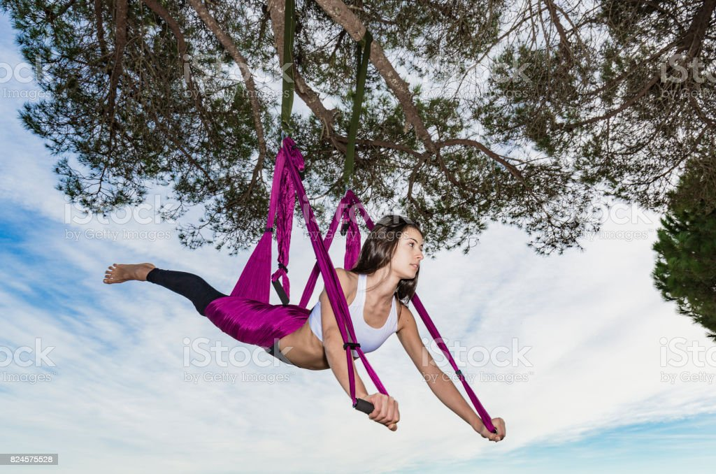 Woman practicing aerial yoga hanging from a tree stock photo