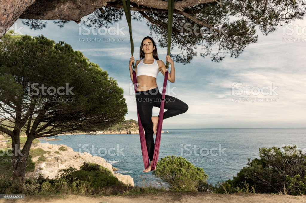 Woman practicing aerial yoga outdoors stock photo