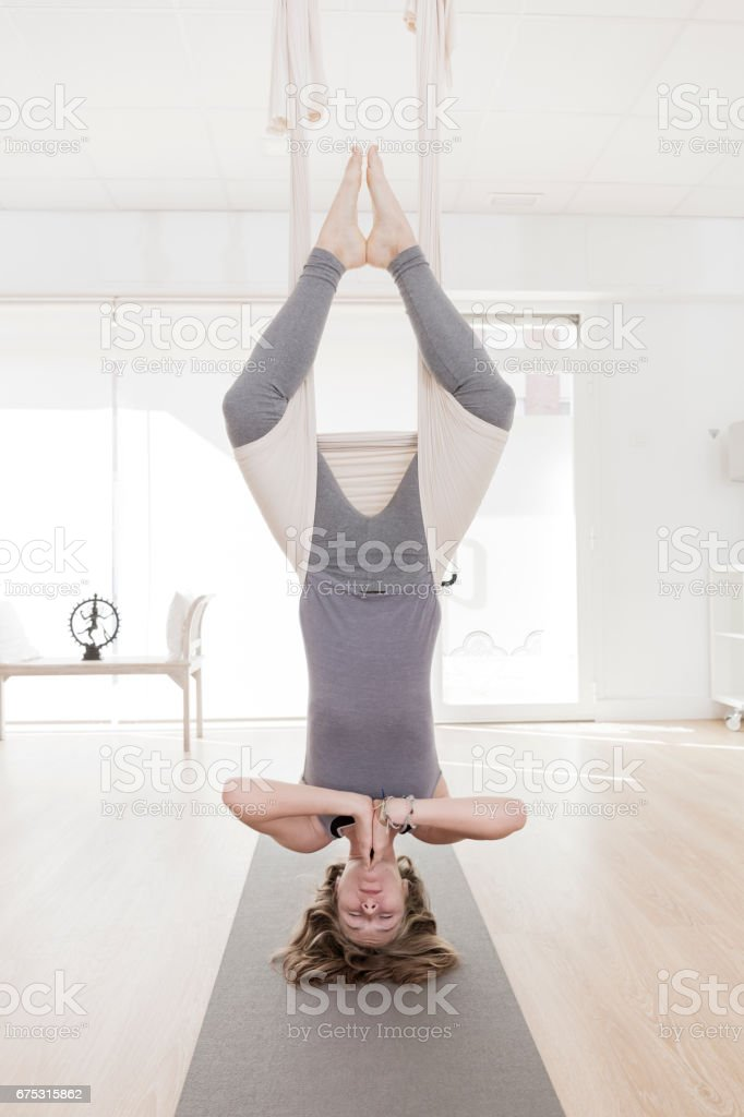 Woman practicing aerial yoga stock photo