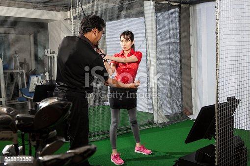 A woman taught me as a man teaching golf at a golf studio.