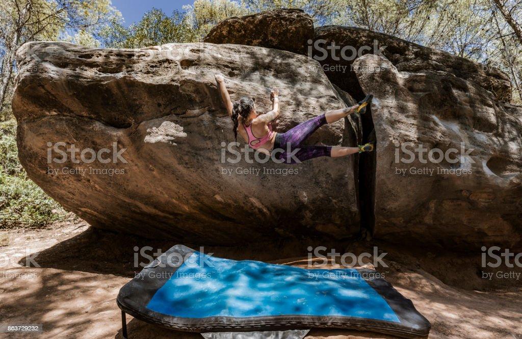 Woman practicing boulder rock climbing stock photo