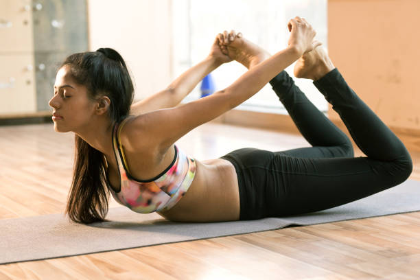 Woman practicing bow yoga pose stock photo