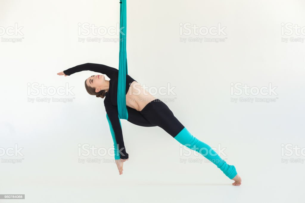 Woman practicing fly yoga over white background stock photo