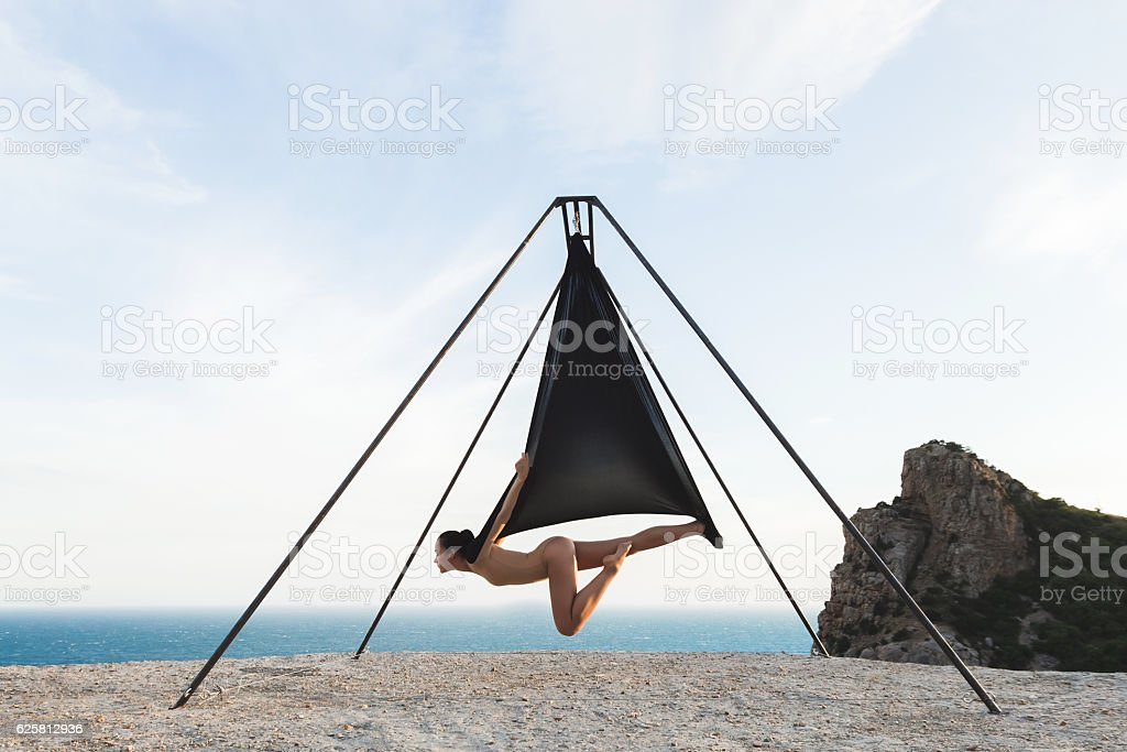 Woman practicing fly-dance yoga poses in a hammock stock photo