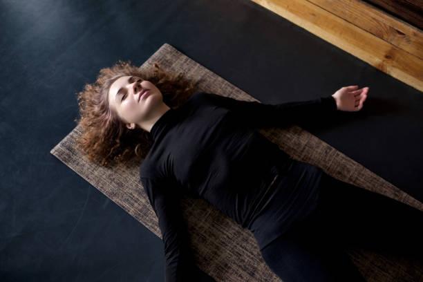 bir yoga stüdyosu shavasana veya kolordu dinlenme egzersiz kadın poz - yatmak stok fotoğraflar ve resimler