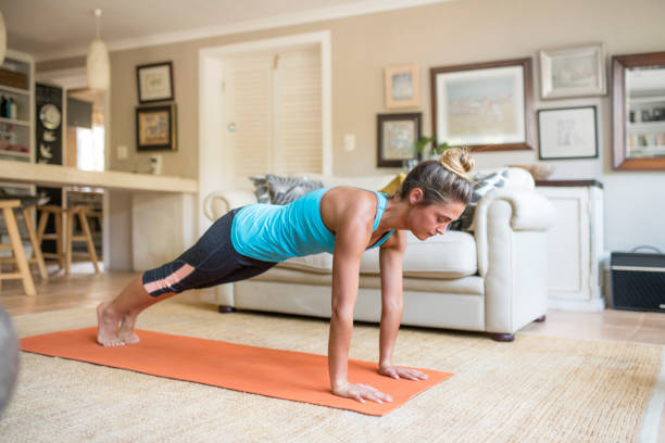 Woman practicing in plank pose on mat at home Full length of woman in plank pose on exercise mat. Confident young female is wearing sportswear. She is practicing yoga at home. sun salutation stock pictures, royalty-free photos & images