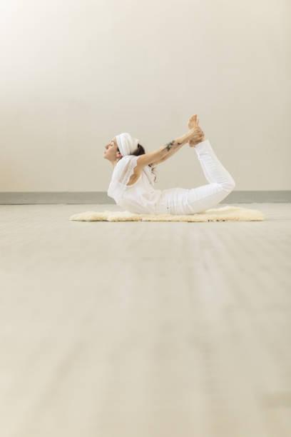 frau kundalini yoga zu praktizieren und bogen stellen - kundalini yoga stock-fotos und bilder