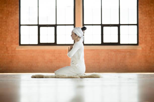 frau üben kundalini yoga und sonne anrede - kundalini yoga stock-fotos und bilder