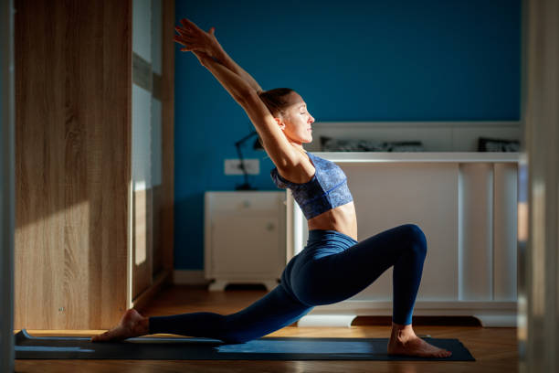 Woman practicing low lunge pose Young attractive woman practicing low lunge pose at home, stretching in Anjaneyasana exercise sun salutation stock pictures, royalty-free photos & images