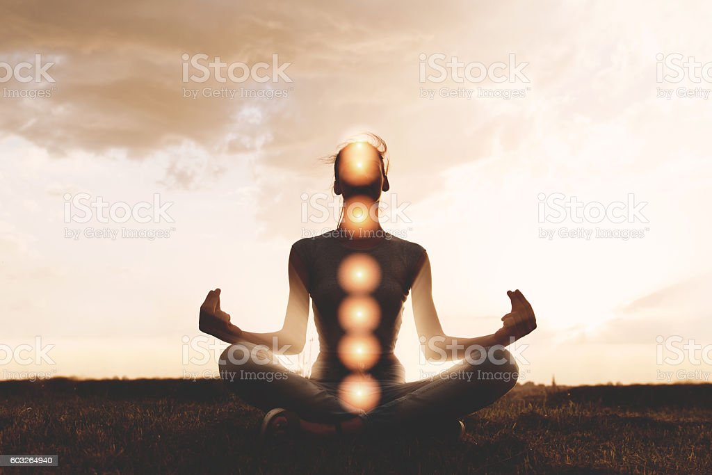 Woman practicing meditation in sunset, with chakras stock photo