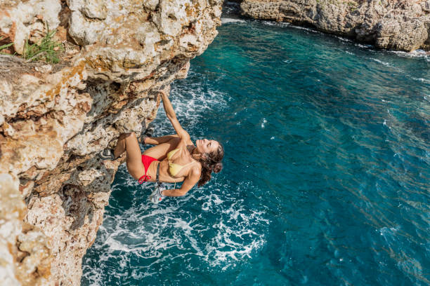 woman practicing psicobloc rock climbing in minorca spain - rock climbing stock photos and pictures