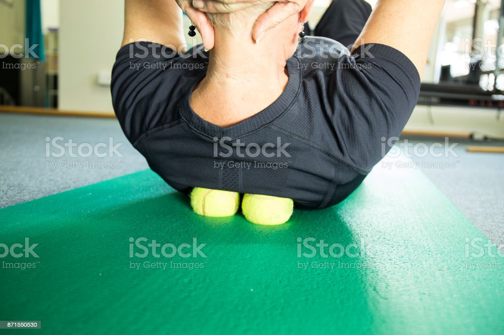 A woman practicing self-massage technique with tennis ball stock photo