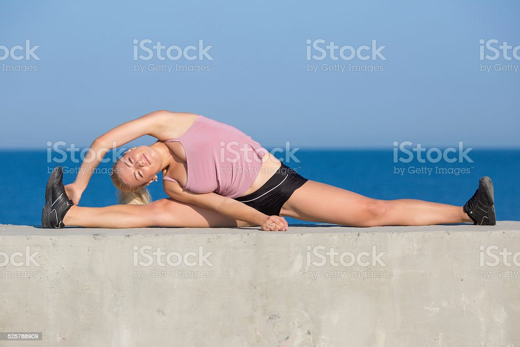 Woman practicing side stretching stock photo