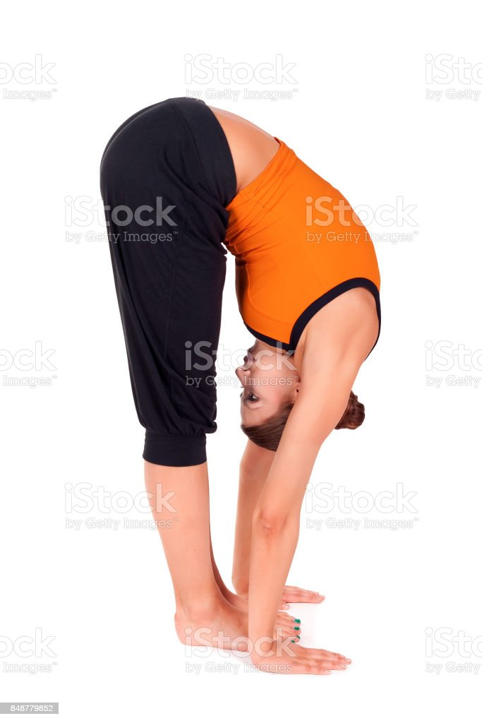 Woman Practicing Standing Forward Bend Yoga Exercise stock photo