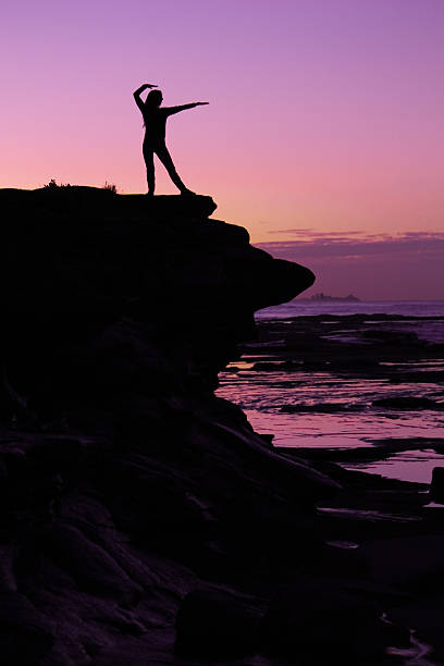 Woman practicing Tai Chi by the beach at dusk stock photo