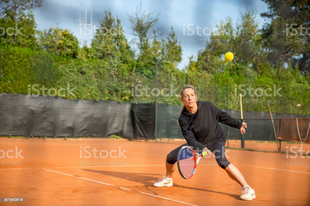 Woman Practicing Tennis On Clay Court stock photo