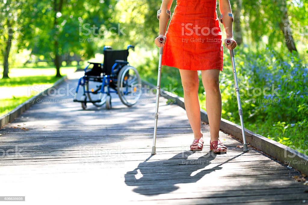 woman practicing walking on crutches stock photo