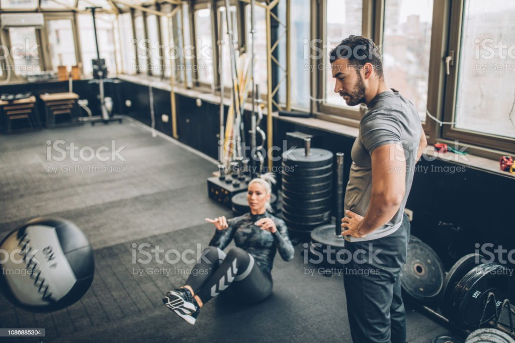 Man fitness trainer and woman in gym, instructor on fitness training...