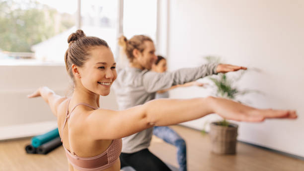 Woman practicing yoga at gym class Smiling sporty woman doing warrior pose in yoga class. Happy young female practicing yoga at gym class. yoga class stock pictures, royalty-free photos & images