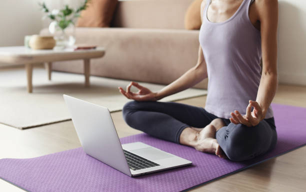 Woman practicing yoga at home. Online video training concept stock photo