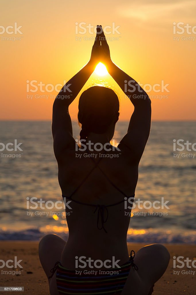 Woman practicing yoga at sunset on the beach stock photo