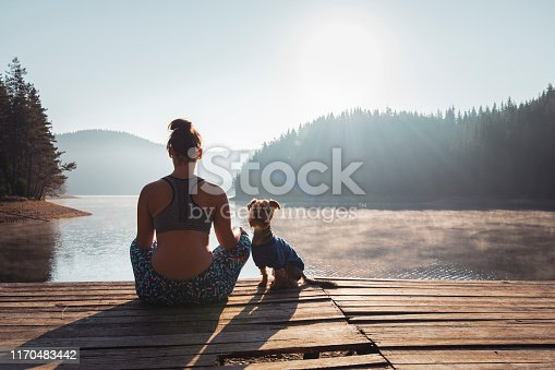 Rear view of woman practicing yoga on wooden pier at mountain lake.