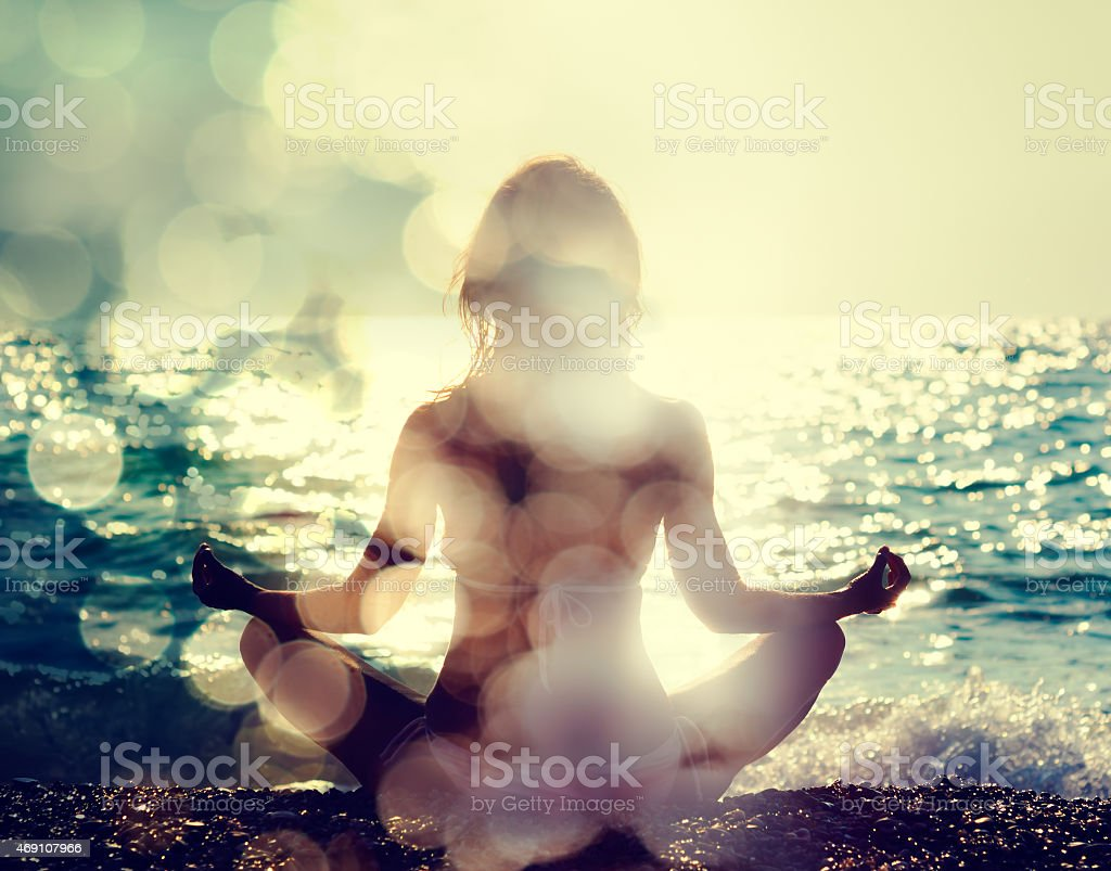 Woman Practicing Yoga by the Sea stock photo