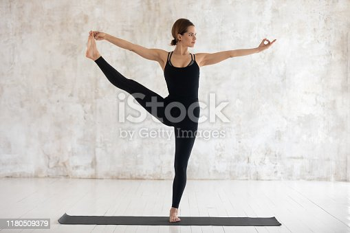 Beautiful woman wearing black sportswear practicing yoga, doing Extended Hand to Big Toe exercise, standing in Utthita Hasta Padangustasana pose, working out at home or in yoga studio with grey walls