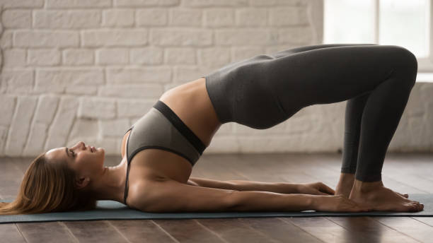 Woman practicing yoga, doing Glute Bridge exercise, dvi pada pithasana Attractive young woman in grey sportswear, leggings and bra practicing yoga, beautiful girl doing Glute Bridge exercise, dvi pada pithasana pose, working out at home or in yoga studio close up shoulder stand stock pictures, royalty-free photos & images