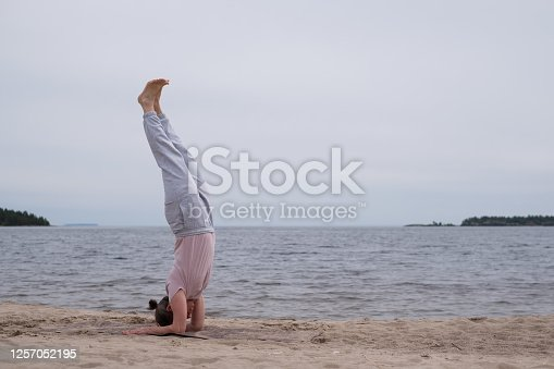 Young woman practicing yoga doing handstand on beach outdoor.