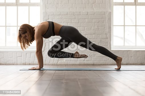 istock Woman practicing yoga, doing Knee to Forehead exercise, Plank pose 1134840955