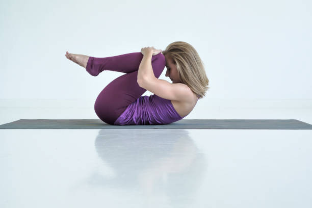 Woman practicing yoga, doing Knees to Chest exercise, Apanasana pose. Young sporty woman practicing yoga, doing Knees to Chest exercise, Apanasana pose. Good posture for improving digestion apanasana stock pictures, royalty-free photos & images