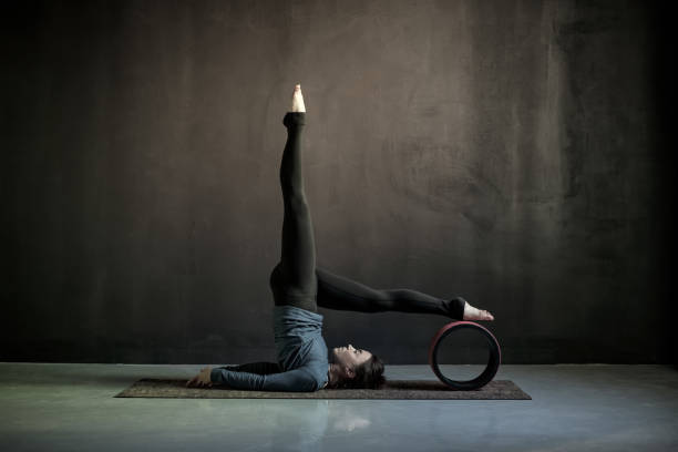 Woman practicing yoga, doing Salamba Sarvangasana exercise Woman practicing yoga, doing Salamba Sarvangasana exercise, supported Shoulder stand pose using wheel props. Studio shot shoulder stand stock pictures, royalty-free photos & images