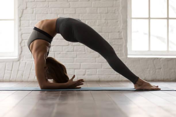 ヨガを実践する女性、dvi パダアヴァンガヴィパリタカラニムドラ dandasana、ブリッジ体操 - 逆張り ストックフォトと画像