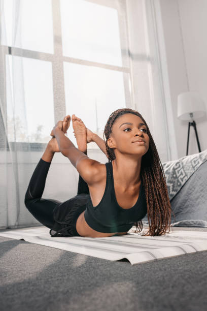 woman practicing yoga in bow pose stock photo