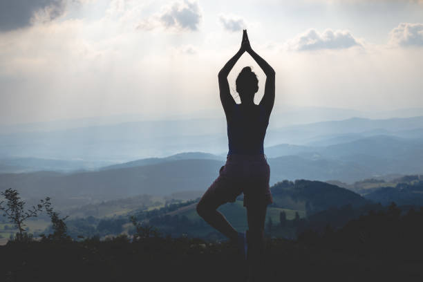 Woman practicing yoga in nature stock photo