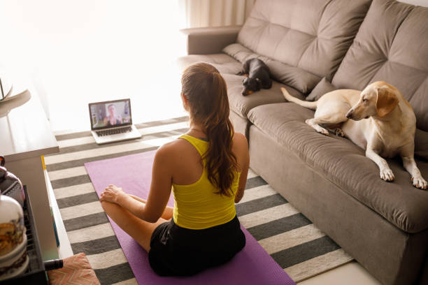 Woman practicing yoga in video conference stock photo