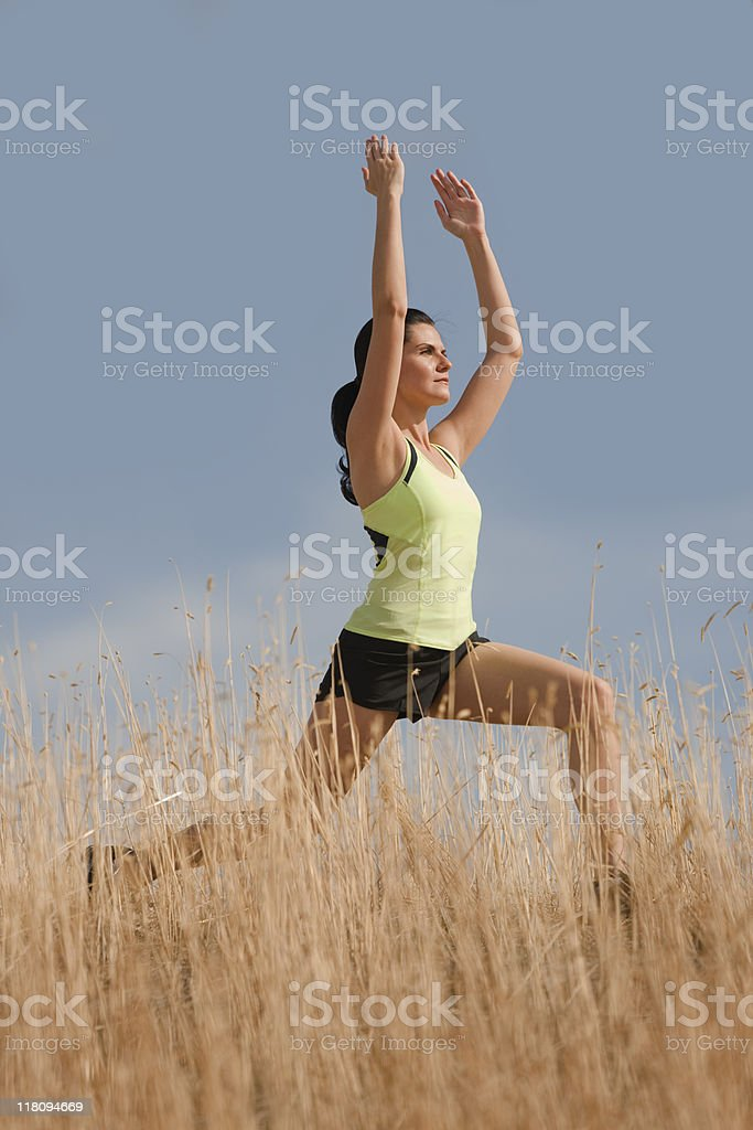 Woman Practicing Yoga In Warrior 1 Position royalty-free stock photo