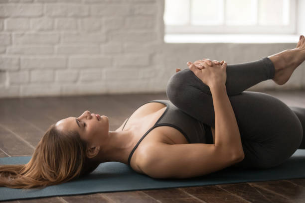Woman practicing yoga, Knees to Chest pose, Apanasana, close up Calm woman with closed eyes practicing yoga, beautiful girl in grey sportswear, pants and bra lying in Knees to Chest pose, doing Apanasana exercise, working out at home or in yoga studio close up apanasana stock pictures, royalty-free photos & images