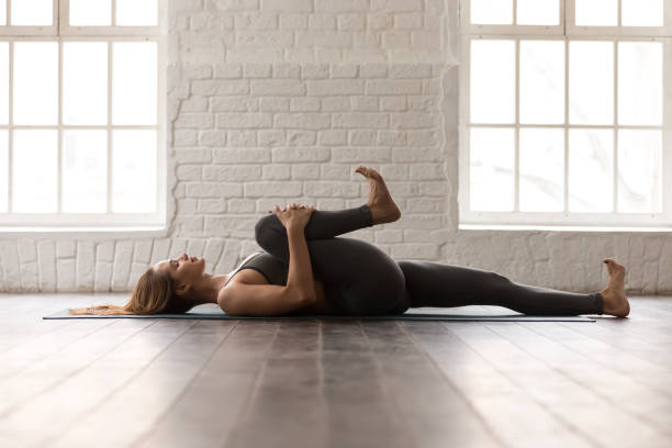 Woman practicing yoga, lying in Knees to Chest pose, Apanasana Calm woman with closed eyes practicing yoga, attractive girl in grey sportswear, pants and bra lying in Knees to Chest pose, doing Apanasana exercise, working out at home or in yoga studio bending stock pictures, royalty-free photos & images